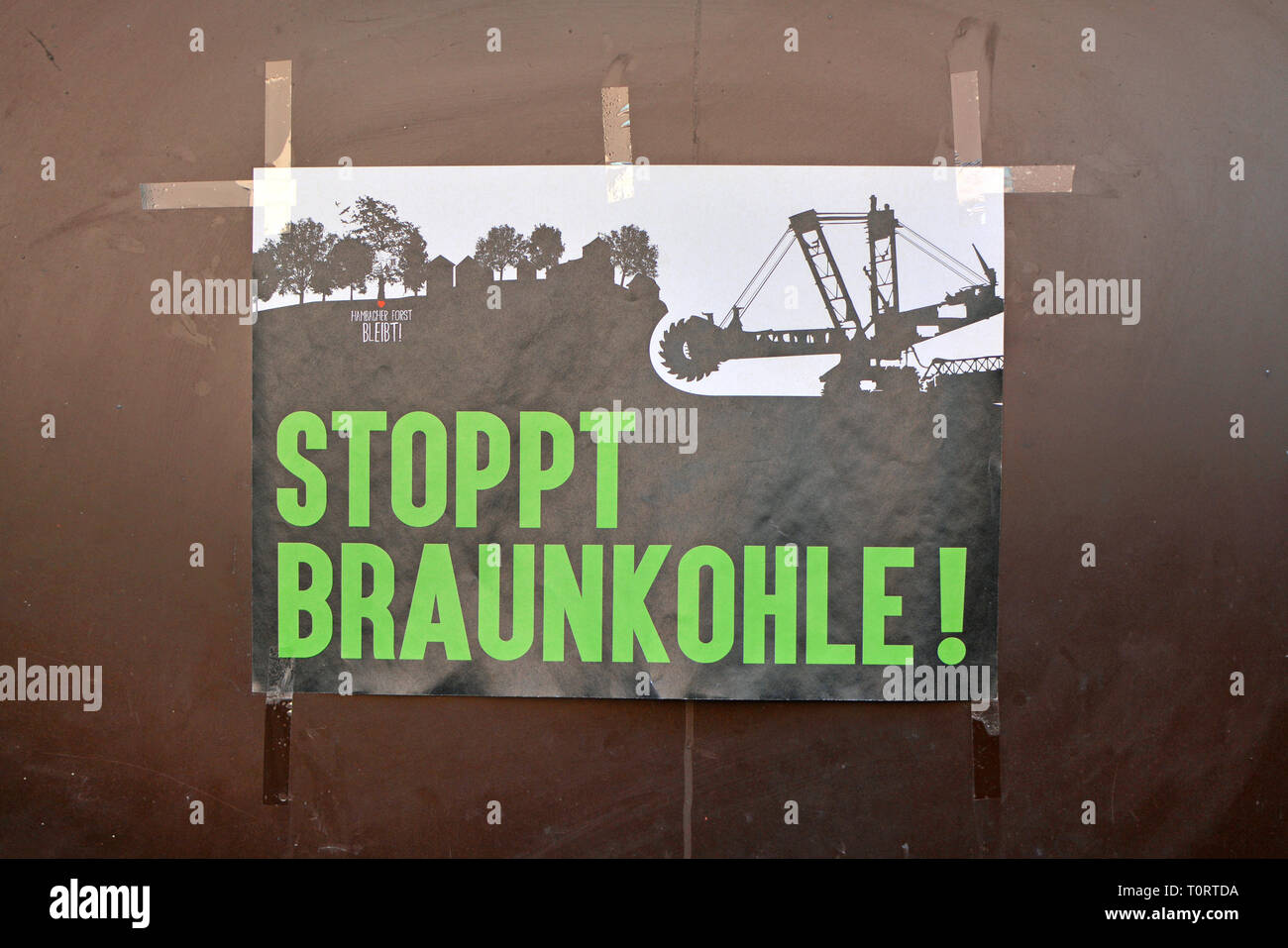 """Protest poster put up on wall saying """"Stop brown coal"""" in bold green letters and """"Hambacher forest stays"""" in upper corner in Germany Stock Photo"""