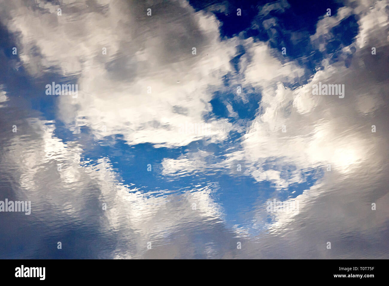 Rain clouds (cumulo nimbus) reflected and distorted in a puddle, so in effect an abstract image of water. - Stock Image