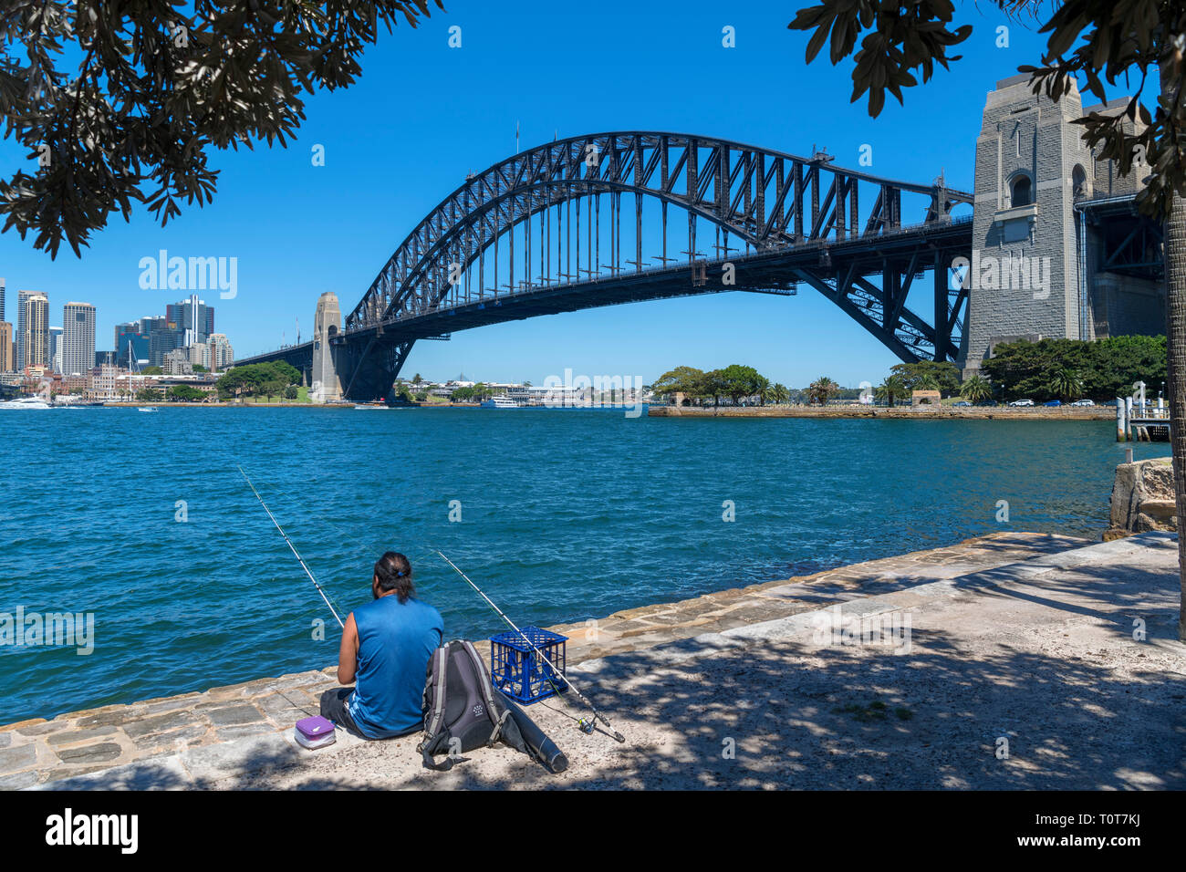 Angler fishing from the waterfront in Kirribilli in front of the Sydney Harbour Bridge, Sydney, Australia - Stock Image