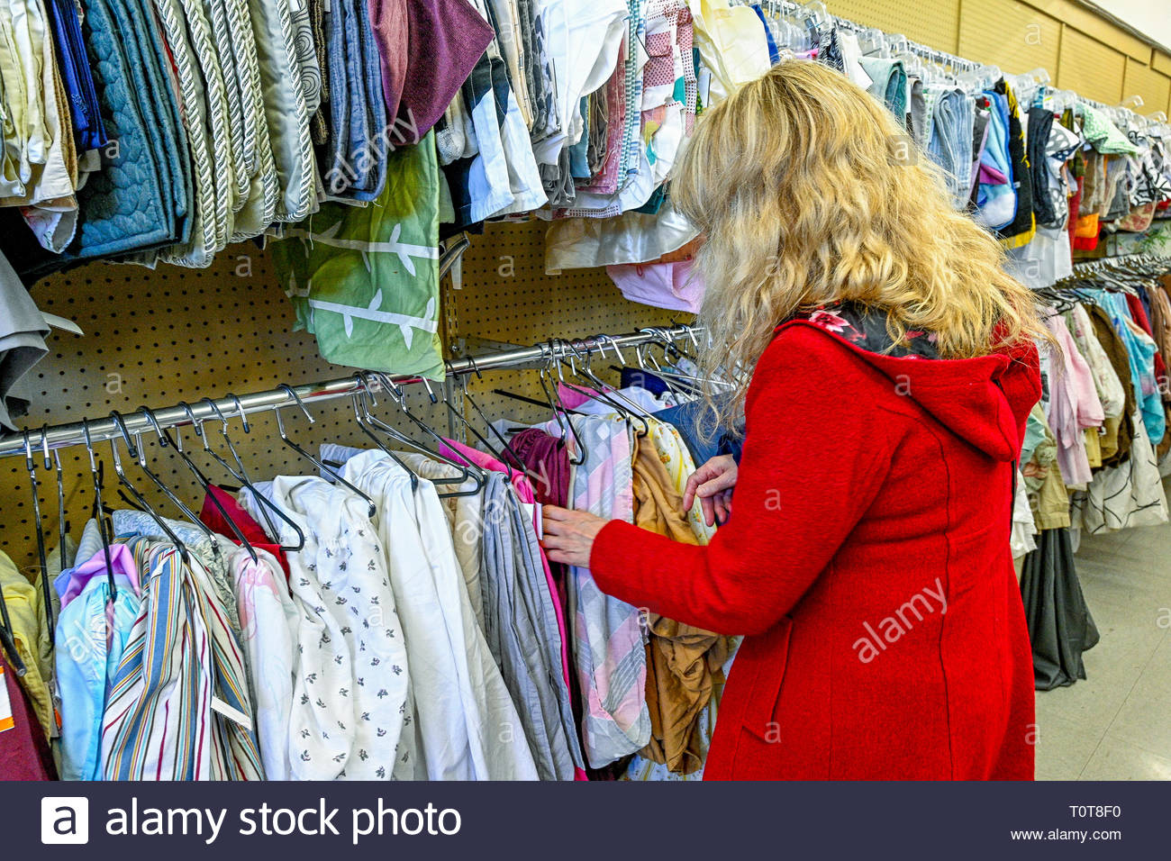 Woman browsing clothes in 2nd hand thrift, goodwill store, shop - Stock Image