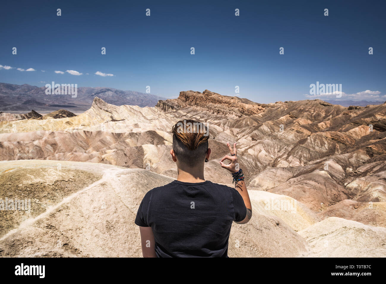 Death Valley and a visitor doing okay gesture with his hand Stock