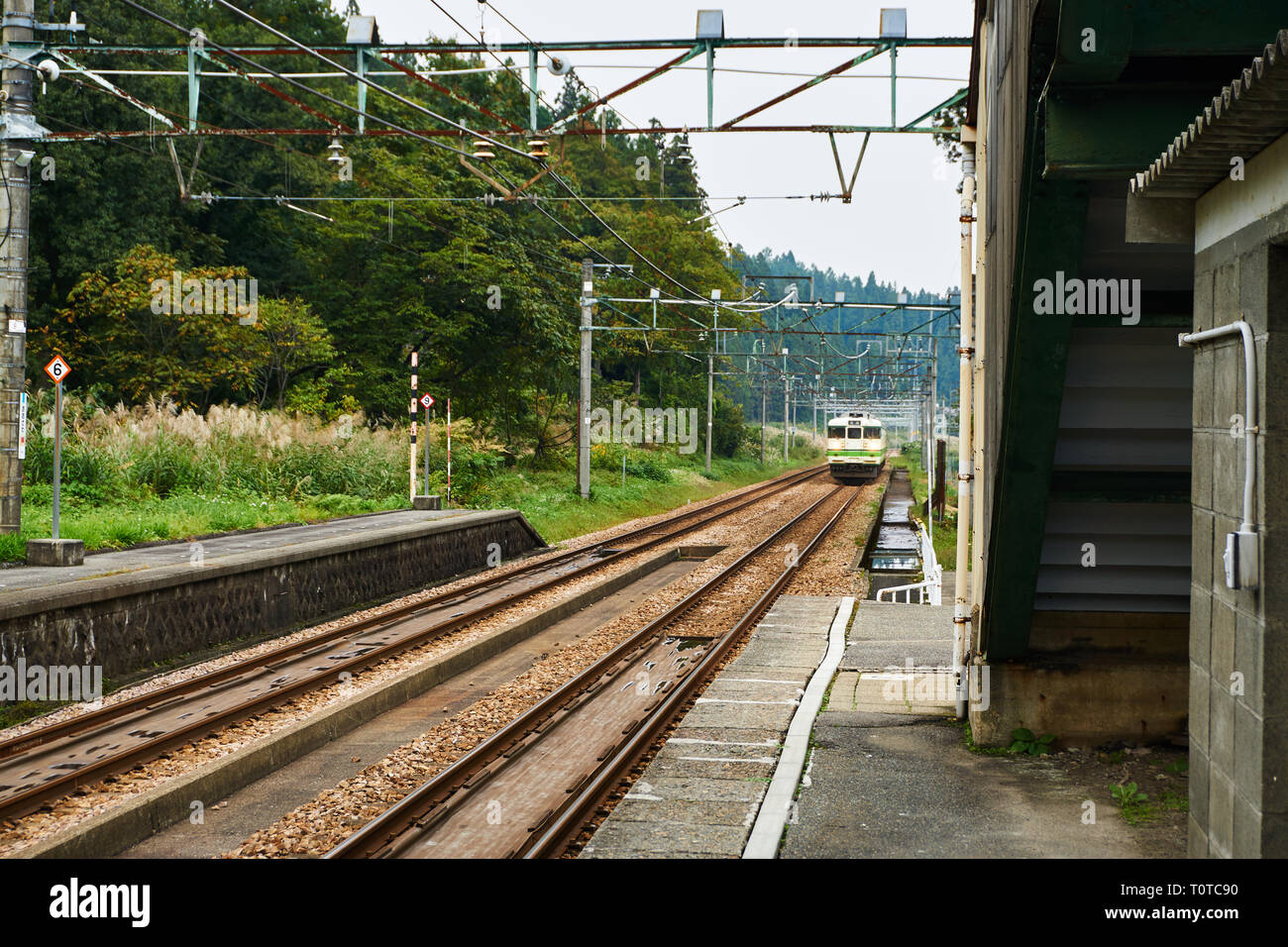 A small train approaches a countryside train station on the JR Joetsu Line in Niigata. - Stock Image