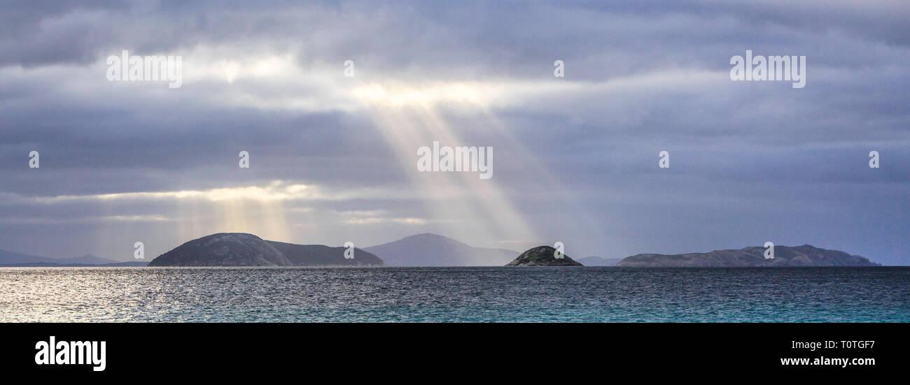 Crepuscular rays over Seal Island, Michaelmas Island and Breaksea Island in Albany, WA - Stock Image