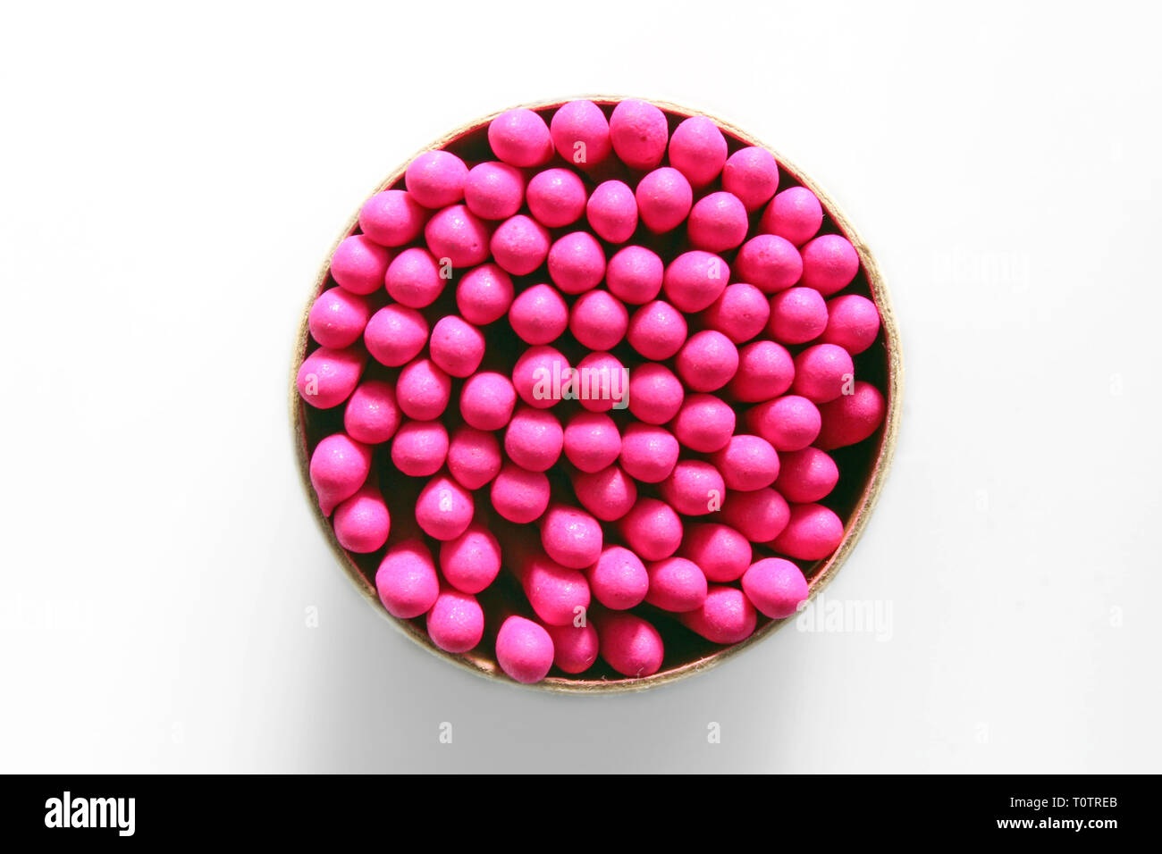 Overhead shot of a bunch of pink-tipped matchsticks, isolated on white background, - Stock Image