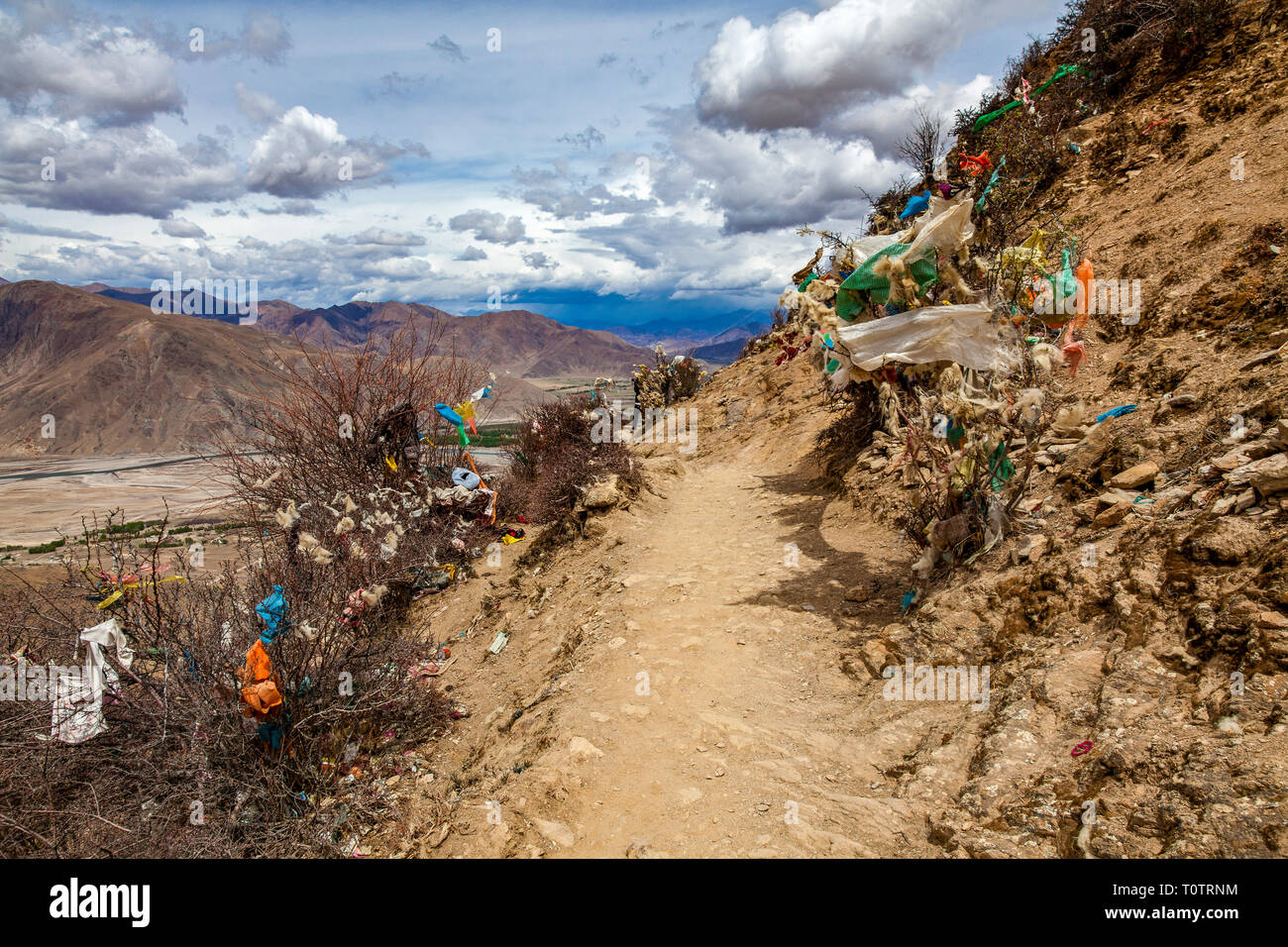Yak hair, sheep wool and discarded prayer flags along the path leading to Ganden monastery.  Outside Lhasa, Tibet, China. - Stock Image