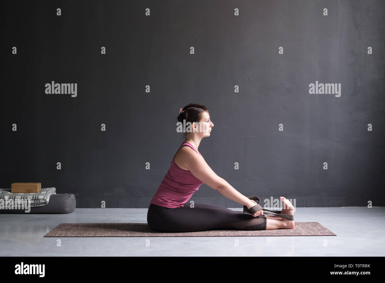 woman practicing yoga, Seated forward bend pose - Stock Image