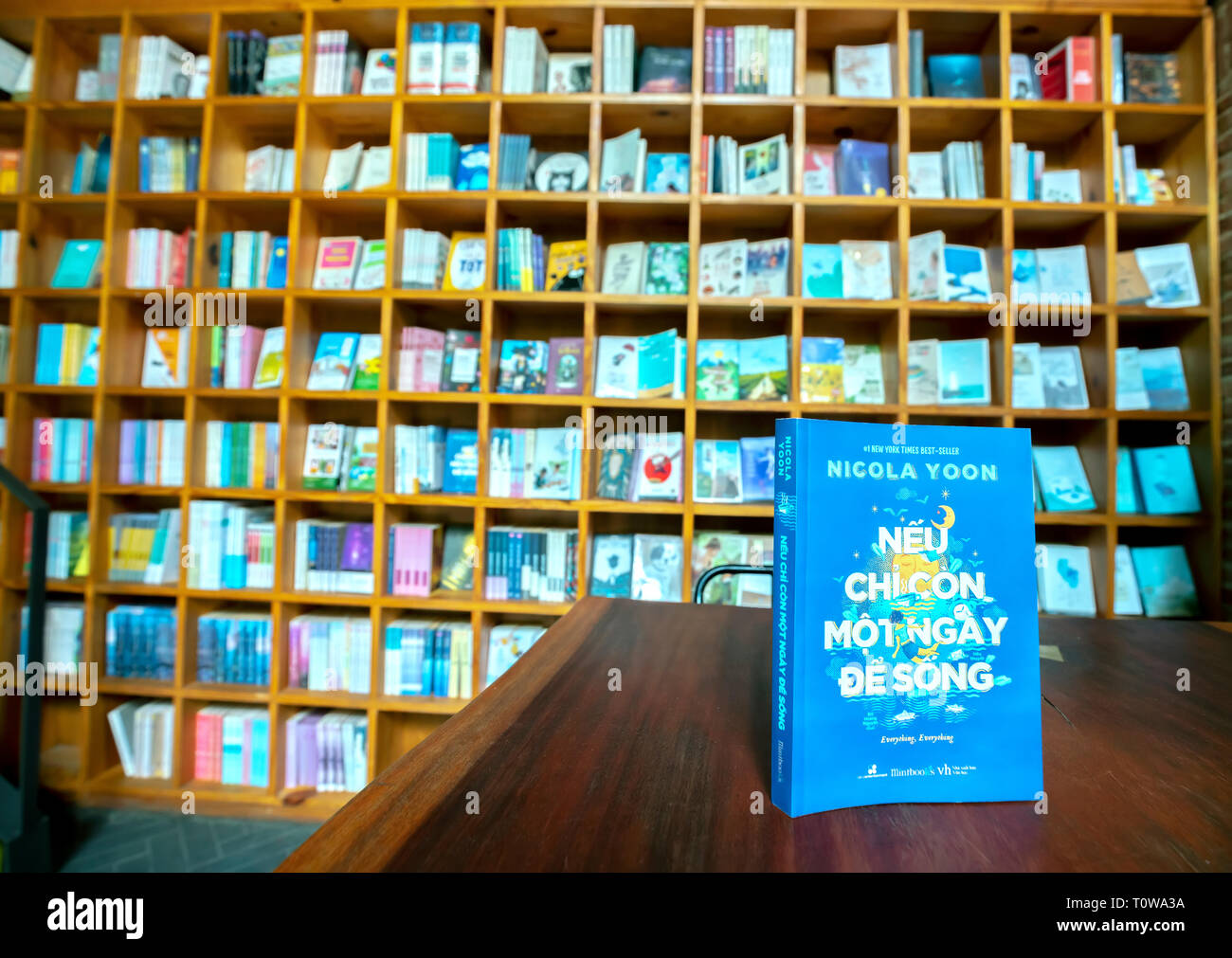 Colorful book shelves packed with books in a library. - Stock Image
