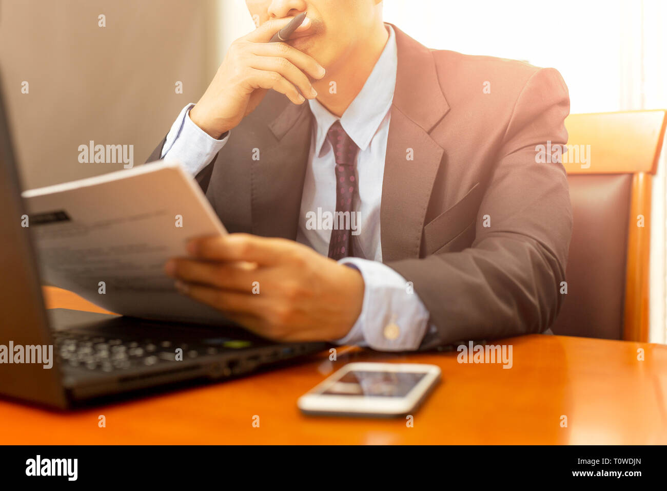 Businessman reading paperwork form with laptop on wooden desk. - Stock Image
