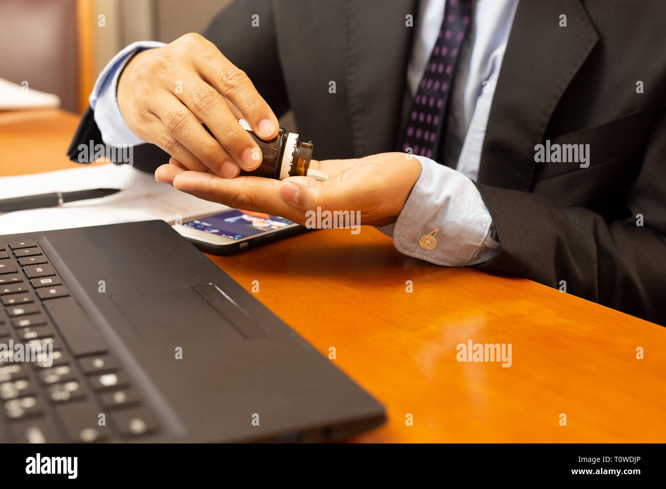 Businessman taking painkiller pill with laptop on wooden table. Stock Photo