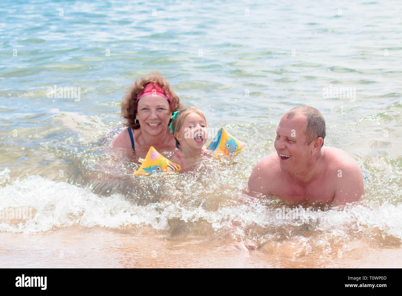 Grandparents And Granddaughter swimming in the sea, they smile and happyness. - Stock Image