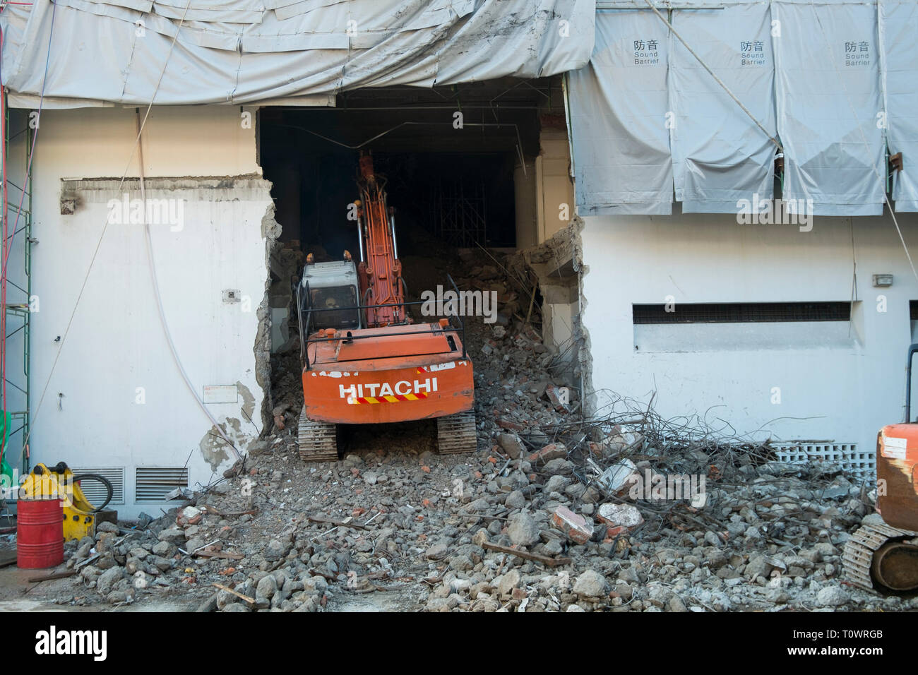 An orange excavator busy clearing out a building being renovated in Kota Kinabalu, Sabah, Borneo, Malaysia. - Stock Image