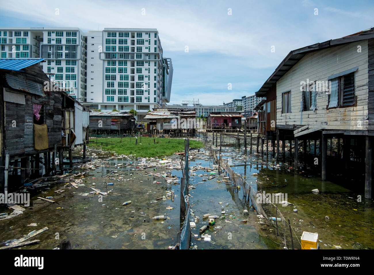 A traditional stilt house water village settlement sits in front of modern development in Kota Kinabalu, Sabah, Borneo, Malaysia. - Stock Image