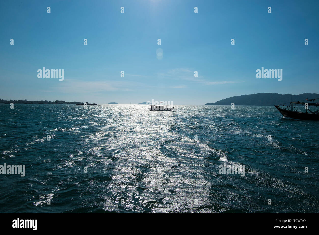 Fishing boats in silhouette on the South China Sea with a sun spike, reflection in Kota Kinabalu, Sabah, Borneo, Malaysia. - Stock Image
