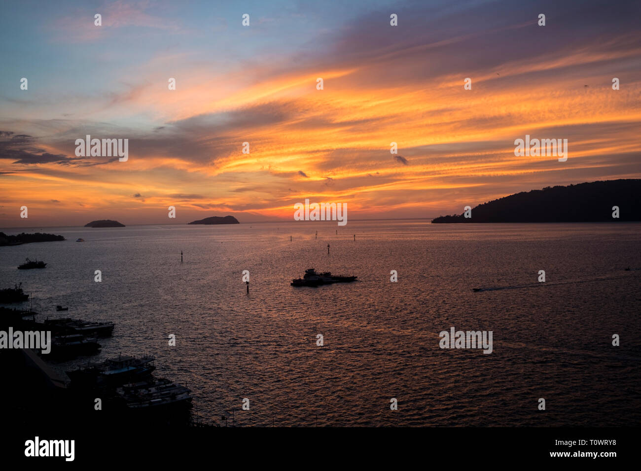 A stunning, beautiful, orange sunset over the South China Sea in Kota Kinabalu, Sabah, Borneo, Malaysia. - Stock Image