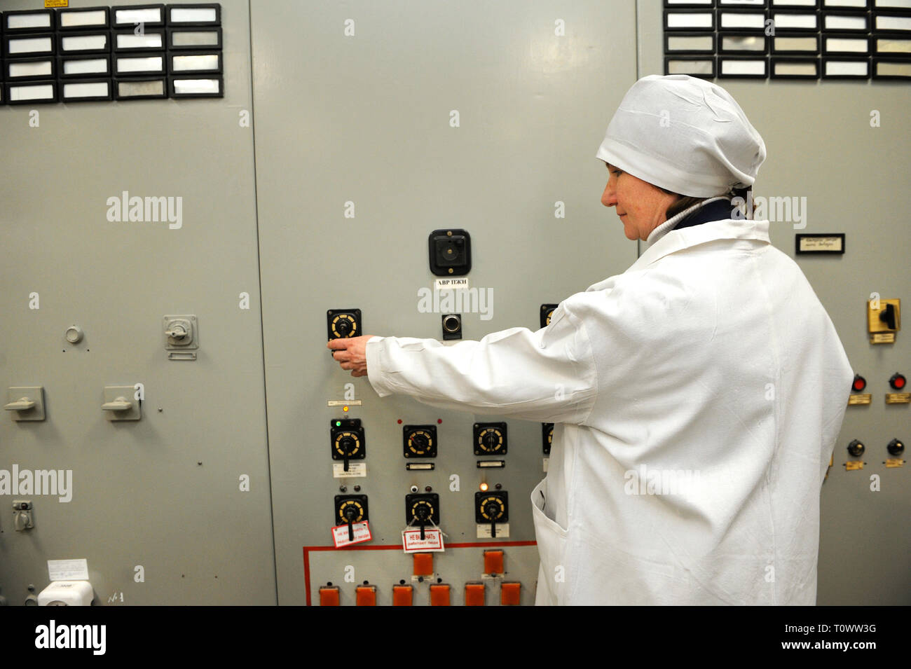 At the control operations room of the Chernobyl Nuclear Power Plant . Operator turning the toggle switch on the main control board. - Stock Image