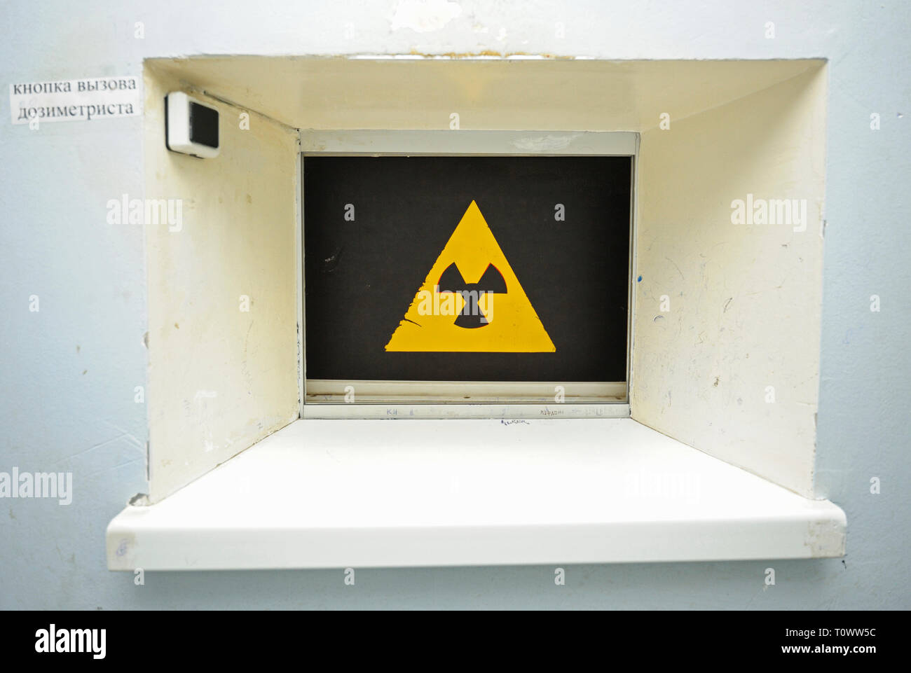 Radiation hazard sign on a window of the radiation control post situated at a passageway of Chernobyl Nuclear Power Plant - Stock Image