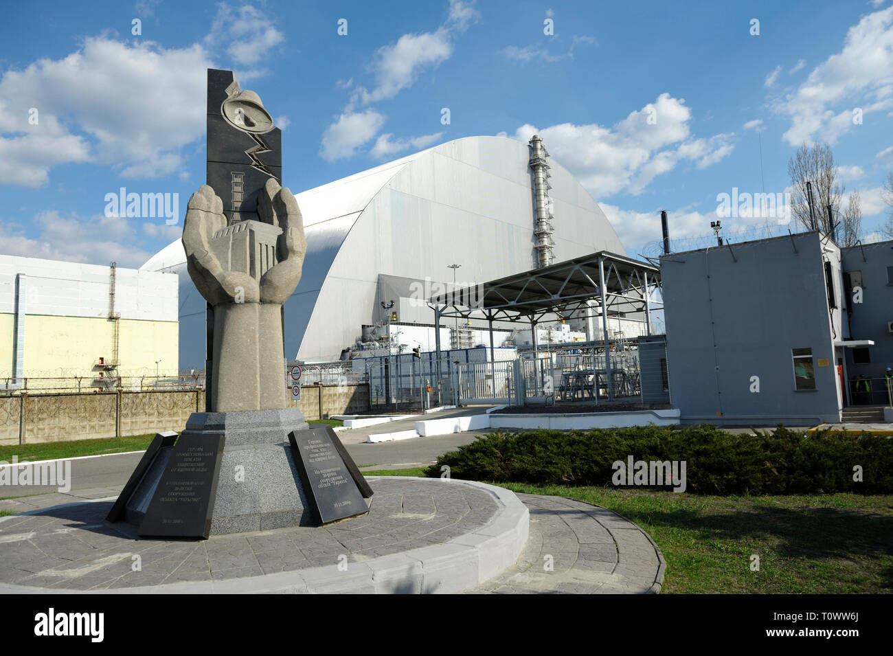 Monument to the Chernobyl Liquidators and New Safe Confinement on a background. April 20, 2018. Chernobyl, Ukraine - Stock Image