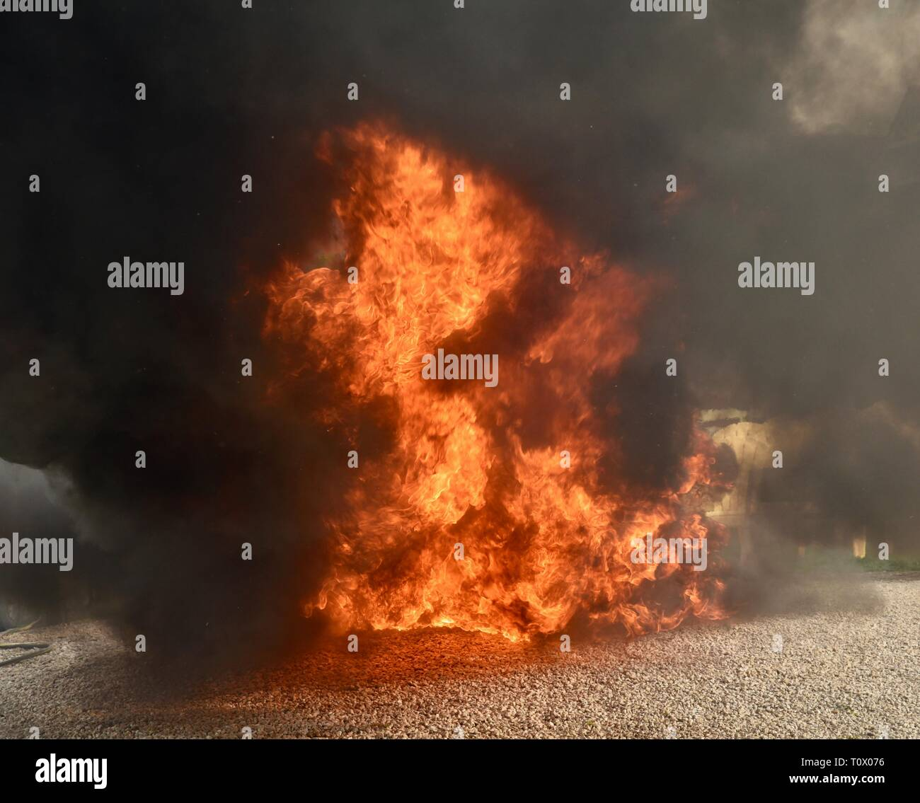 Explosive, dangerous inferno fire with undulating, dancing flames and blackening smoke rising and billowing cloud and plumes of smoke. Stock Photo