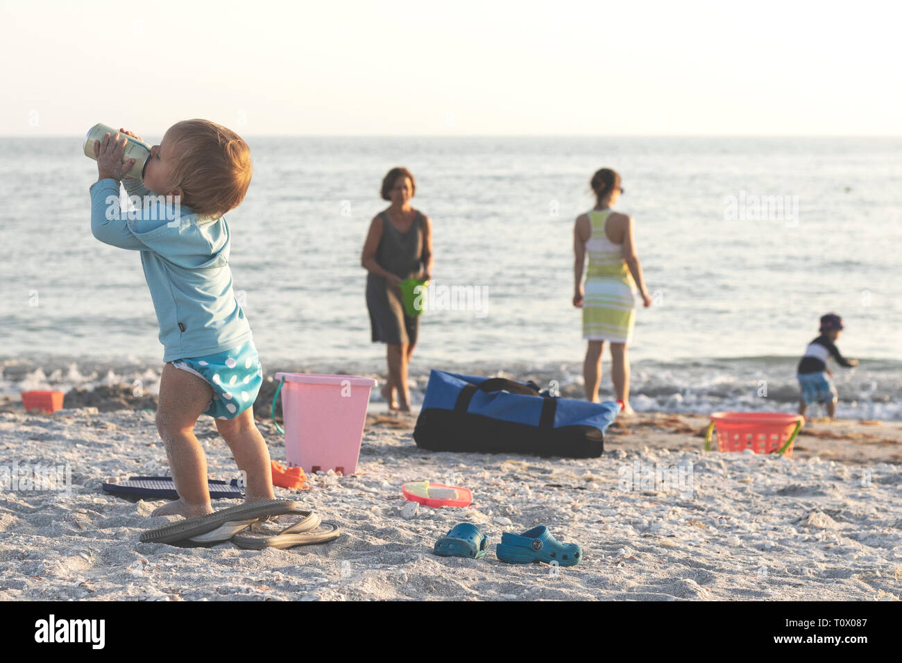Family on the beach with children in the background drinking - Stock Image
