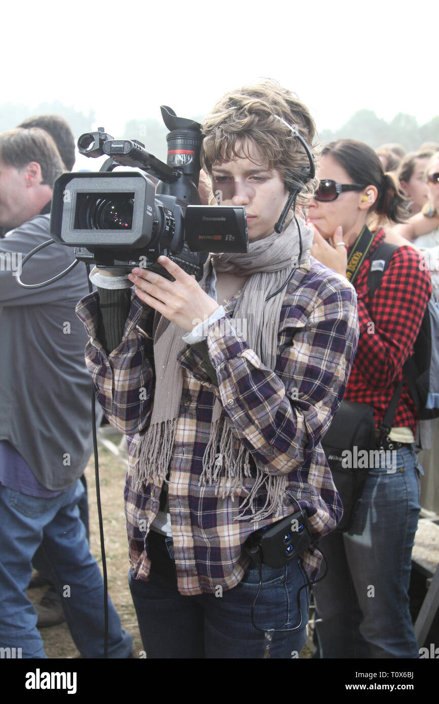 A videographer is shown taping a 'live' concert performance during an outdoor summer festival event. - Stock Image