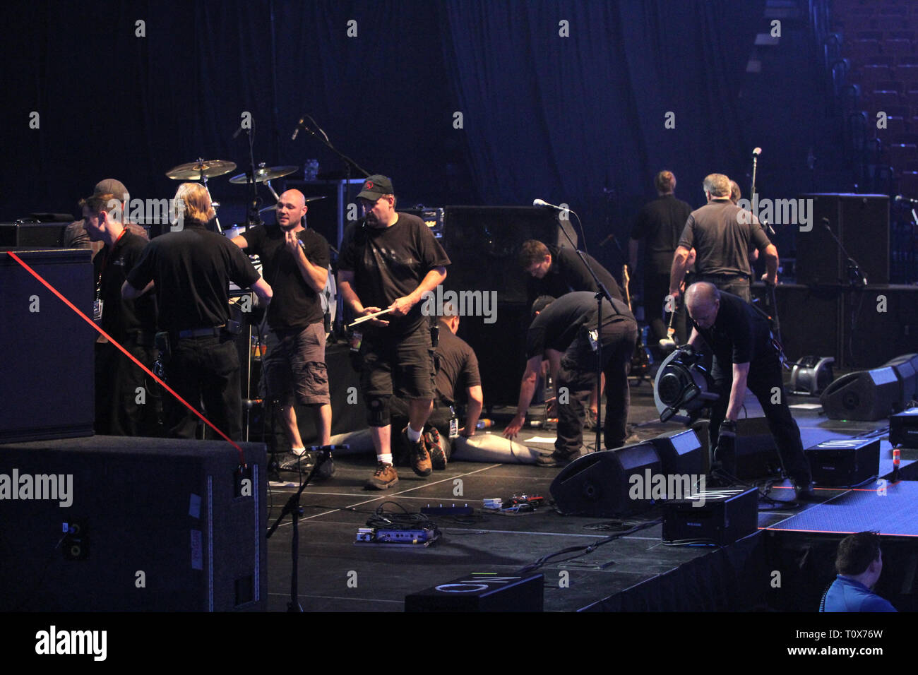 Stage hands are shown working on an equipment changeover in between acts a 'live' concert performance. - Stock Image