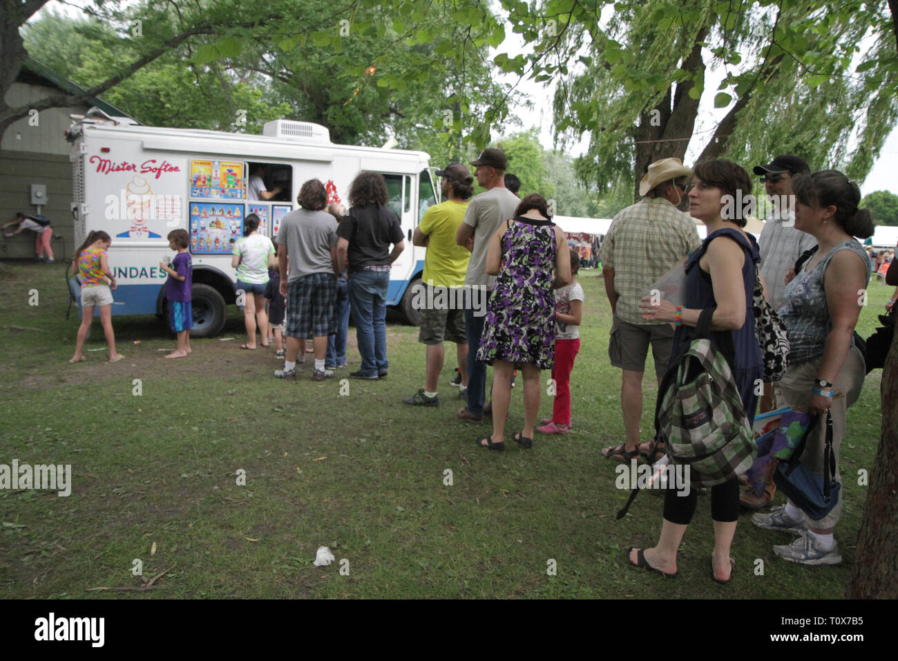Concert goers are shown waiting in line for Mister Softee during an outdoor music festival. Stock Photo