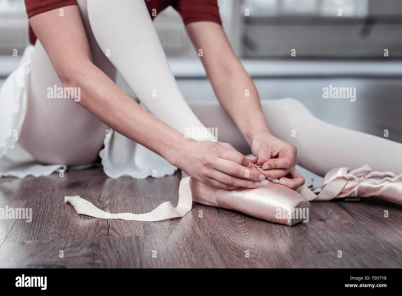 Nice young woman putting on her ballet shoes - Stock Image