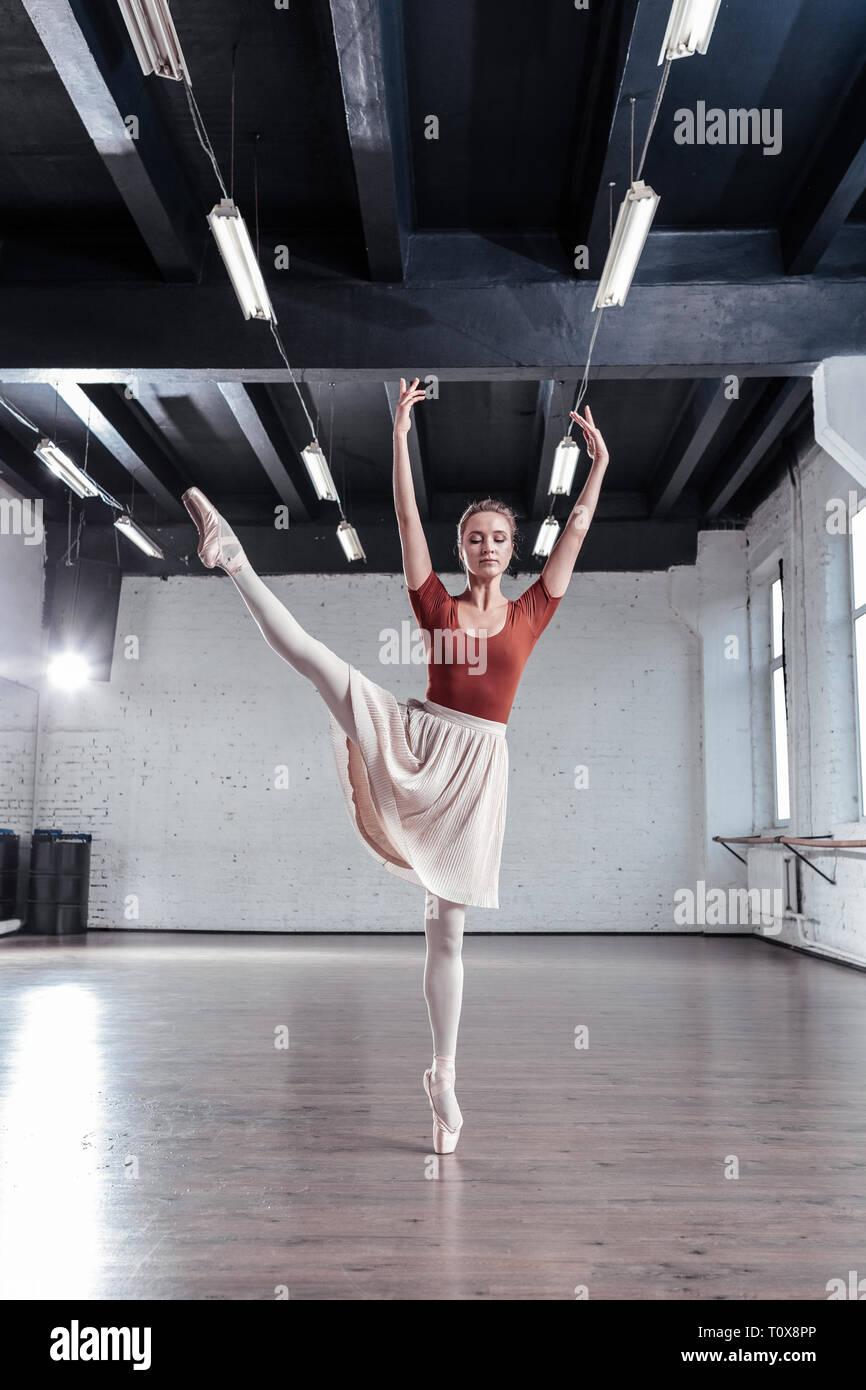 Beautiful graceful ballerina getting pleasure from dancing - Stock Image