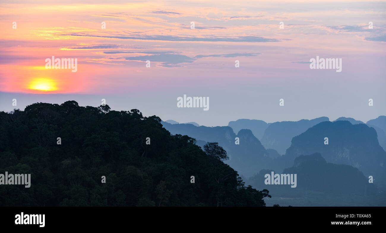 Stunning sunset behind some beautiful limestone mountains. Picture taken from the Tiger Cave Temple (Wat Tham Sua) Krabi, Thailand. - Stock Image