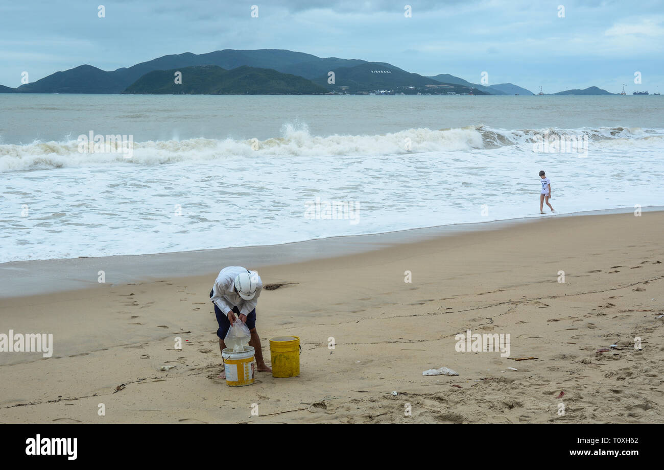 Nha Trang, Vietnam - Jan 26, 2016. People on sand beach with the storm in Nha Trang, Southern Vietnam. - Stock Image