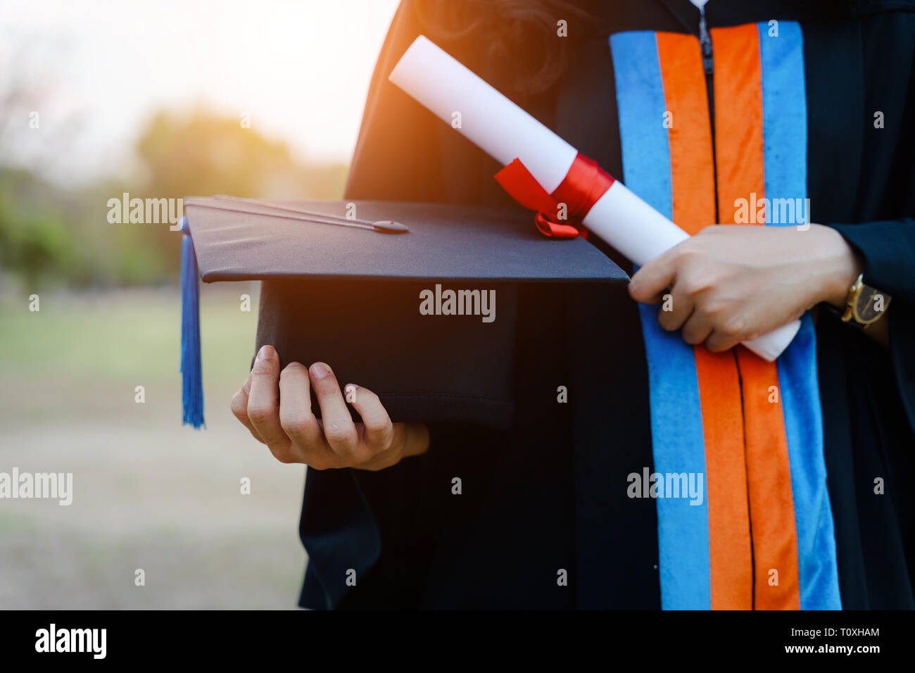 Female university graduate celebrates graduation ceremony receiving degree certificate happily with excitement. - Stock Image
