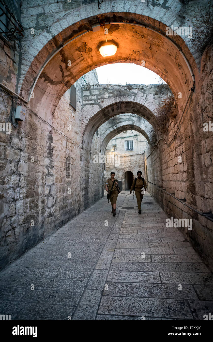 White and black women in military uniform walking in narrow street of the old city of Jerusalem. Jerusalem, Israel: 24 October, 2018. - Stock Image