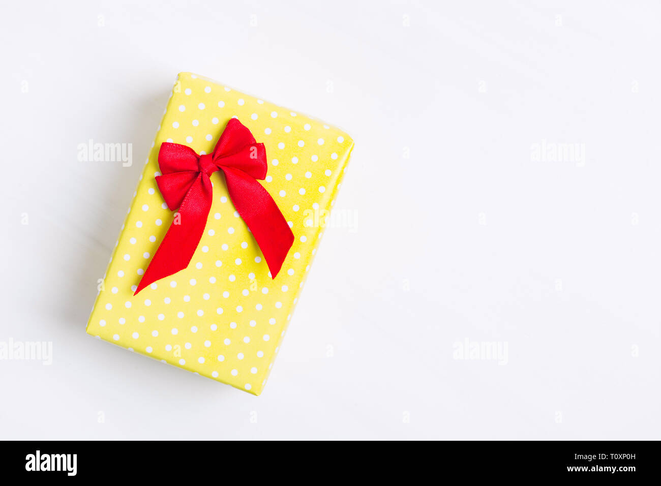 Yellow spotted present with red bow over white textured background, happy birthday, holiday gift, copy space, flat lay style Stock Photo