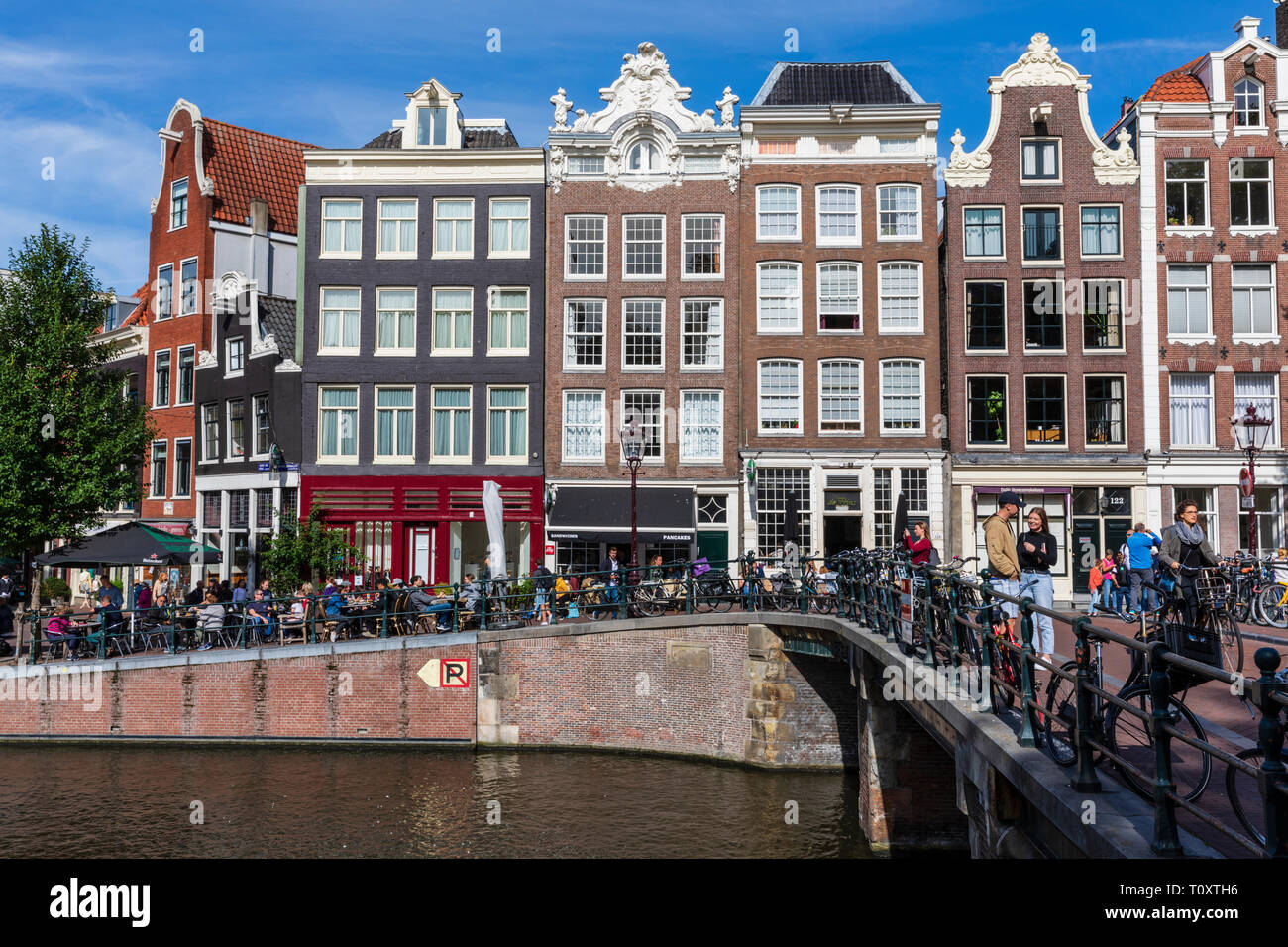 Typical Dutch houses, cafes and shops along the Prinsengracht Canal in Amsterdam, The Netherlands. - Stock Image