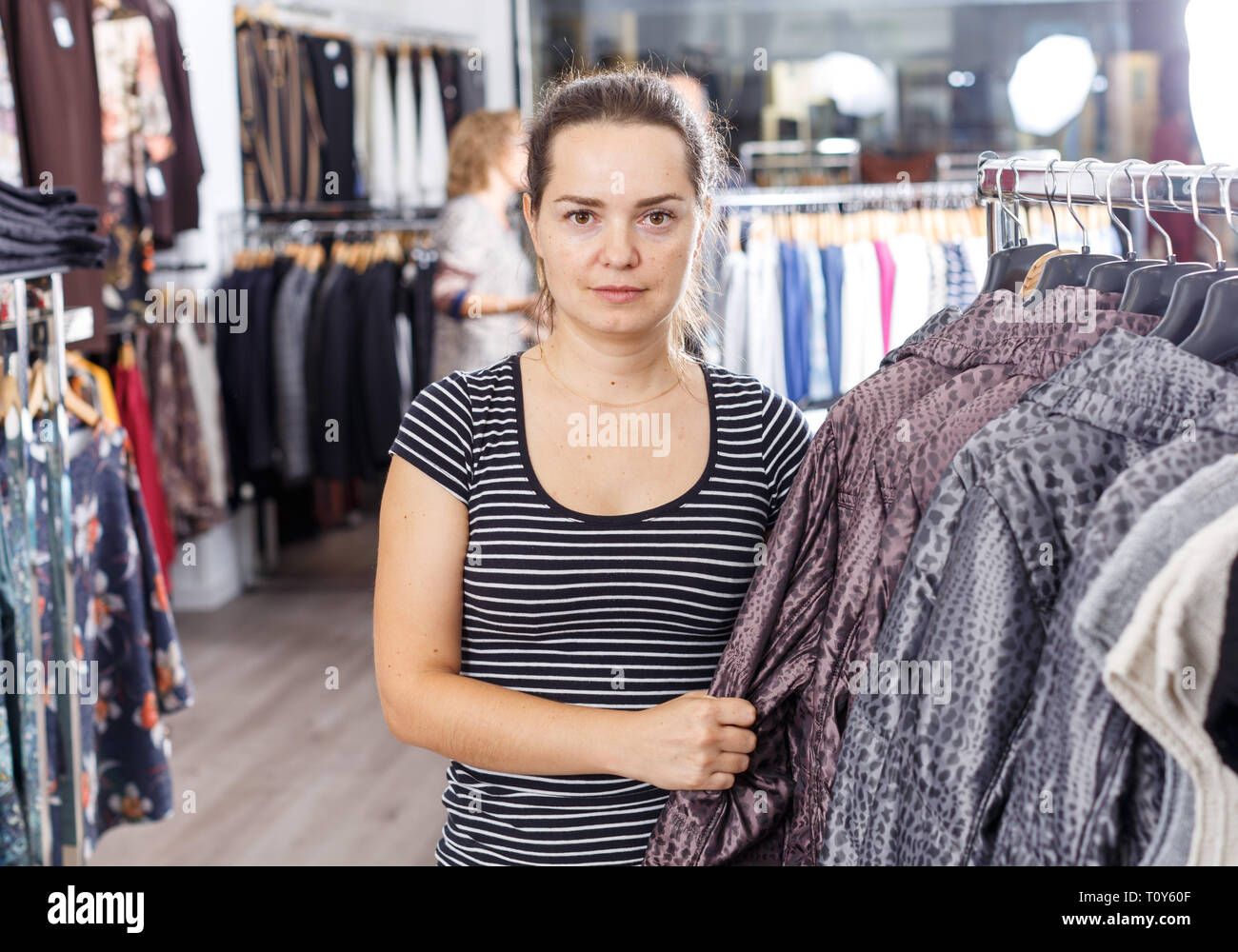 Young attractive woman choosing new overcoat in clothing store - Stock Image