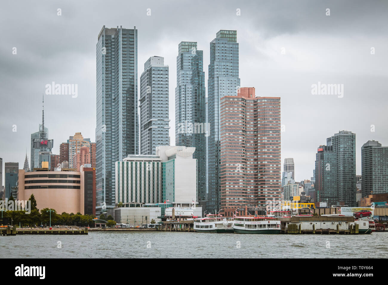 Skyscrapers cluster along the river in New York City. - Stock Image