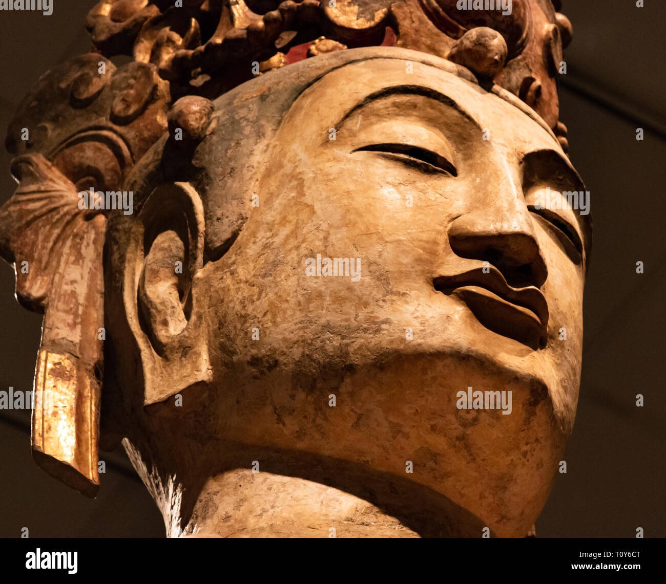 A close up of the face of a giant Buddha on display at the Metropolitan Museum of Art in New York City. - Stock Image