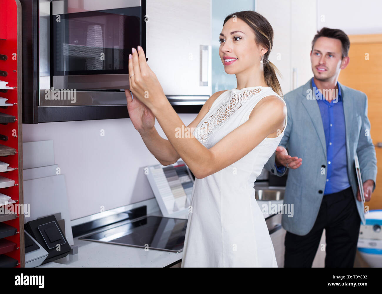 Successful young seller and happy woman at kitchen furniture