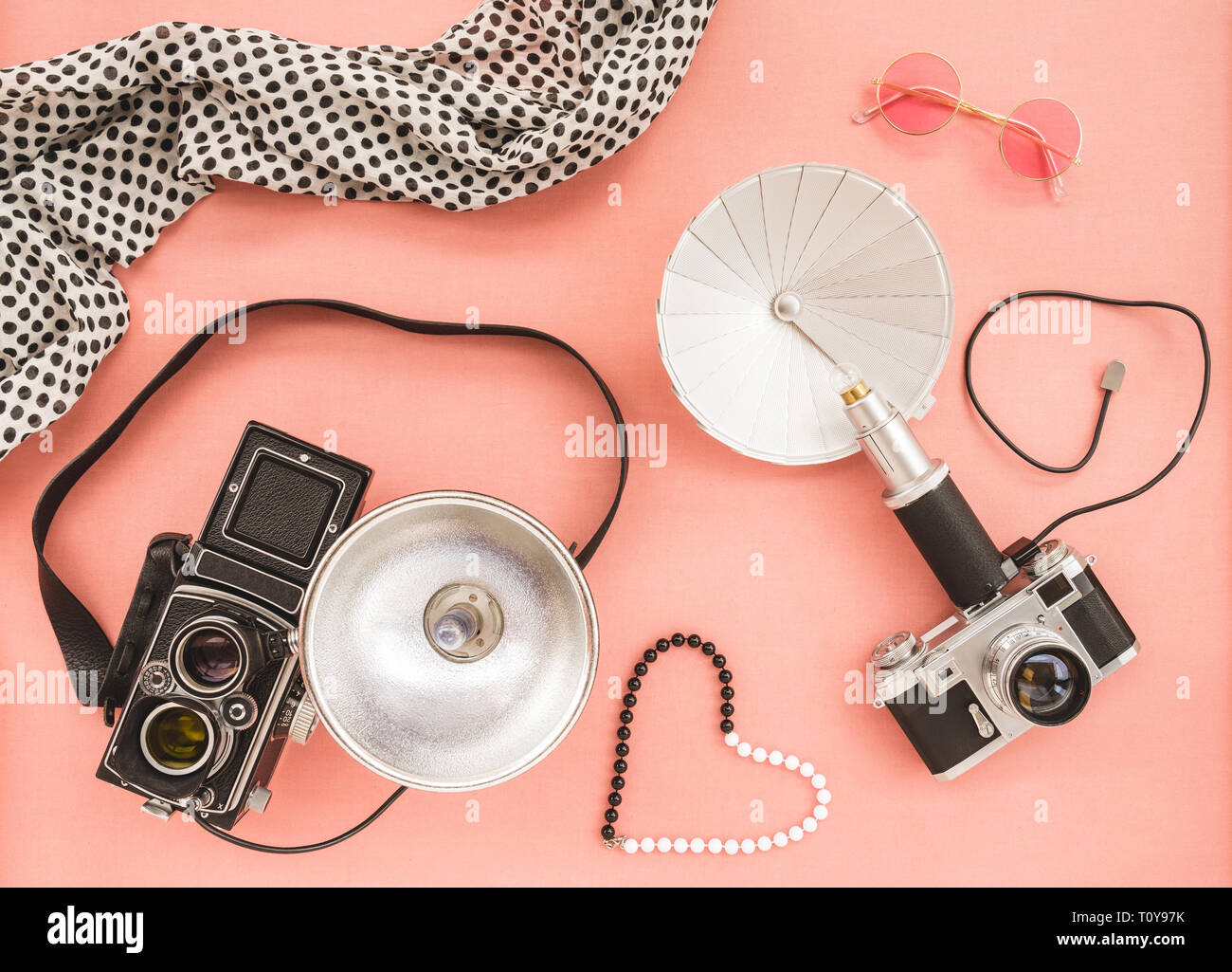 Vintage photo cameras with flashes, on pink canvas background. Stock Photo