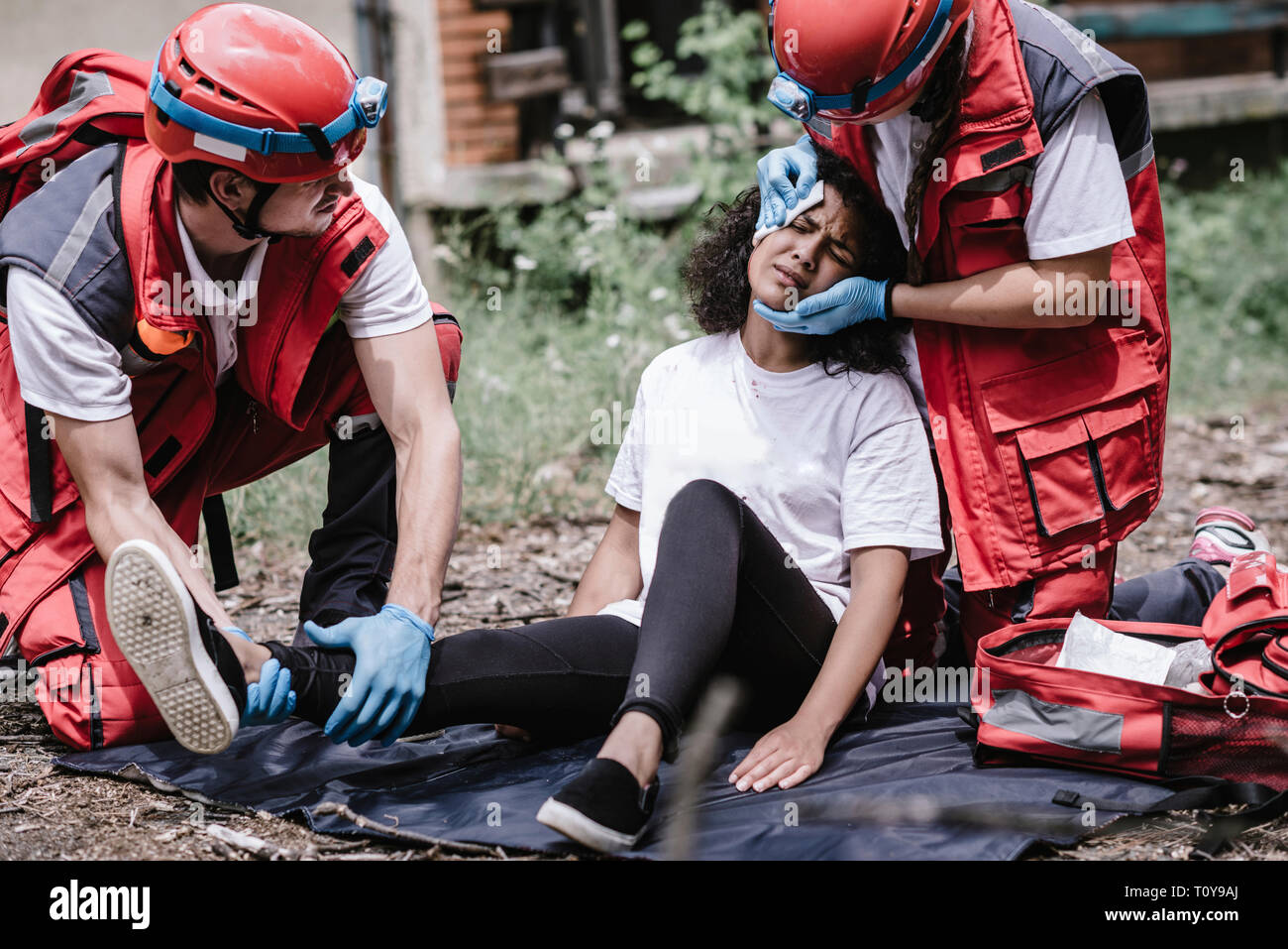 Disaster relief, rescue team helping injured woman. - Stock Image