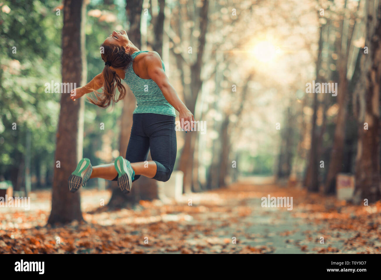Woman doing star jump outdoors, in public park. - Stock Image