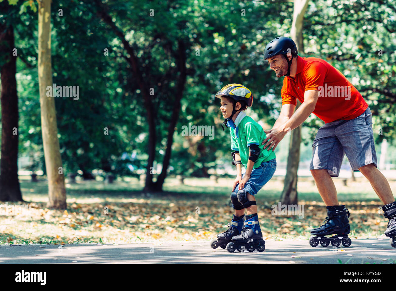 Father and son roller skating in park. Stock Photo