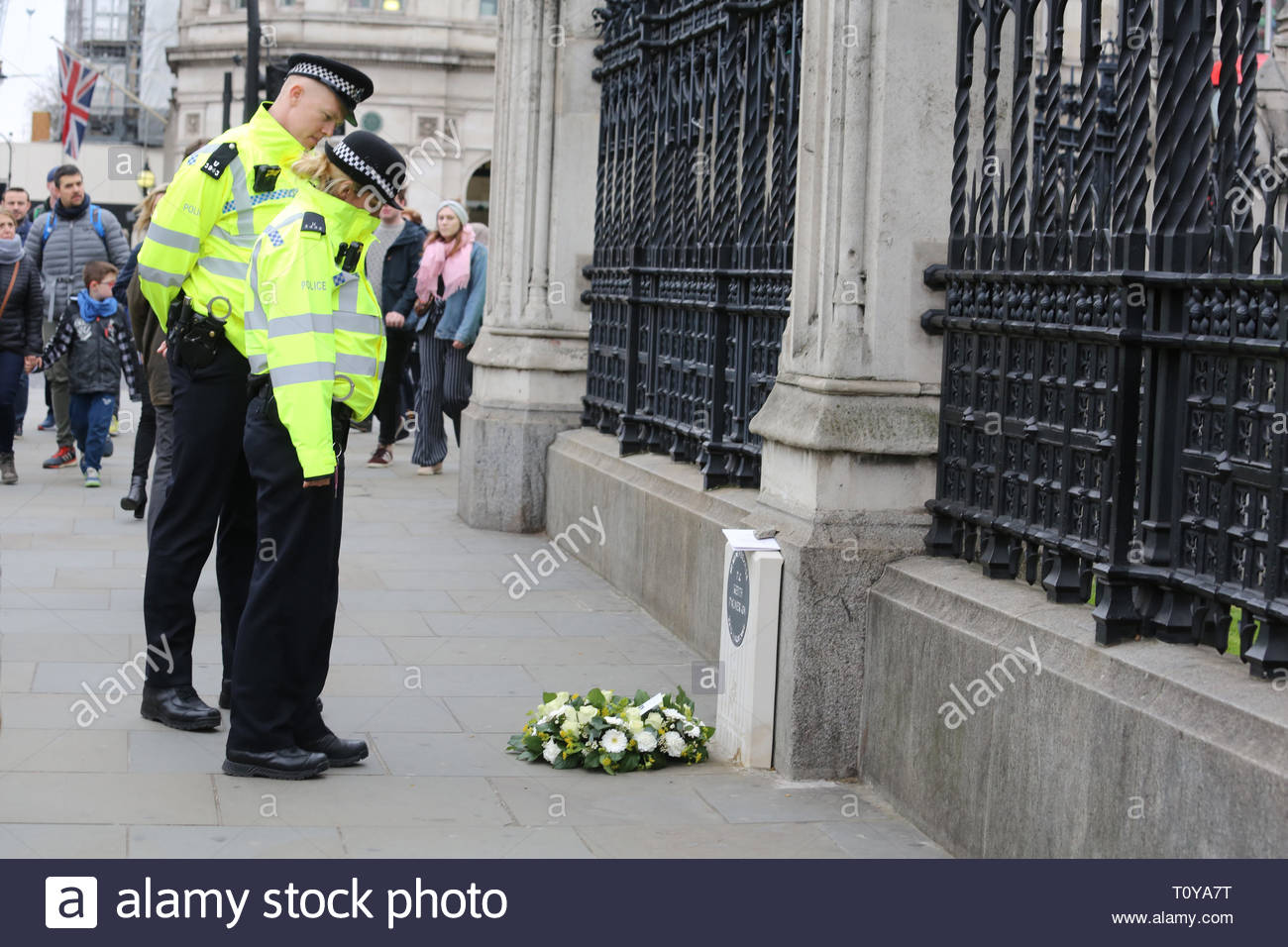 London, UK. 22nd Mar, 2019. Police constables pause at the memorial to PC Keith Palmer in Westminster. Today is the second anniversary of his death which occurred during the attack on London Bridge and parliament. A freshly-laid wreath has been placed there in his memory. Credit: Clearpix/Alamy Live News - Stock Image