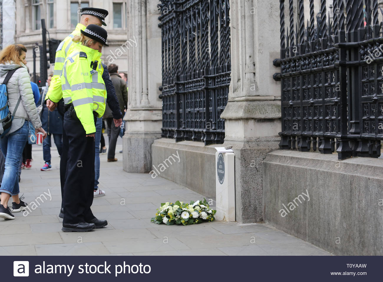 London, UK. 22nd Mar, 2019. Police constables pause at the memorial to PC Keith Palmer in Westminster. Today is the second anniversary of his death which occurred during the attack on London Bridge and fresh flowers have been placed there. Credit: Clearpix/Alamy Live News - Stock Image