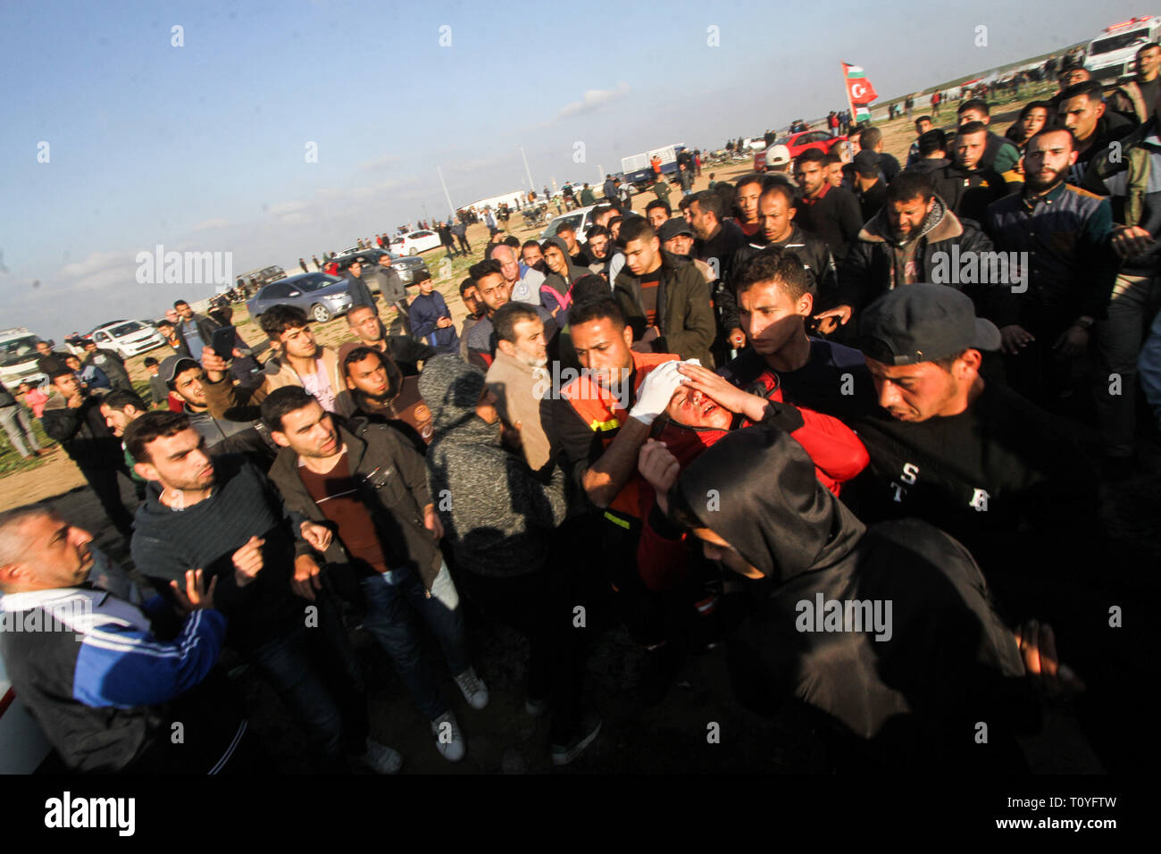 March 22, 2019 - Gaza, 22th March 2019. A number of Palestinian demonstrators are injured in clashes with the Israeli army in the Malika district on the east of Gaza City during this Friday 51st Great March of Return rally. Thousands of demonstrators had gathered at several points on the Gaza-Israeli borders with some hurling rocks and burning tires, and with Israeli troops firing live ammunition, rubber-coated steel bullets, and tear gas at protesters. According to the Gaza Health Ministry, 30 Palestinians were shot and injured by Israeli live fire, while dozens of others suffered from tear-g Stock Photo