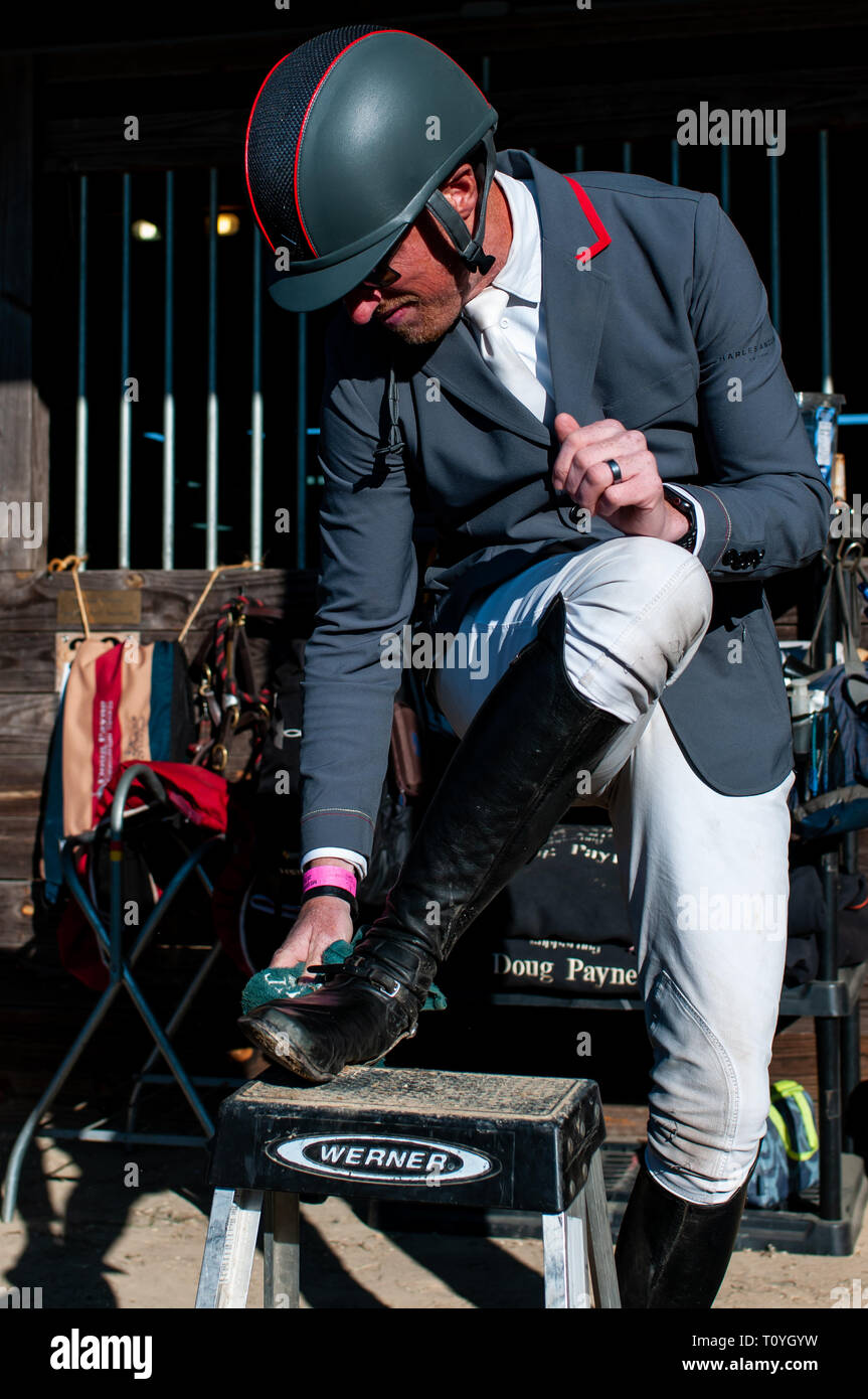 Raeford, North Carolina, USA. 22nd Mar, 2019. March 22, 2019 - Raeford, N.C., USA - DOUG PAYNE of the United States puts the finishing touches on his boots before competing in the CCI3-S show jumping division at the sixth annual Cloud 11-Gavilan North LLC Carolina International CCI and Horse Trial, at Carolina Horse Park. The Carolina International CCI and Horse Trial is one of North America's premier eventing competitions for national and international eventing combinations, hosting International competition at the CCI2*-S through CCI4*-S levels and National levels of Training through Advan - Stock Image