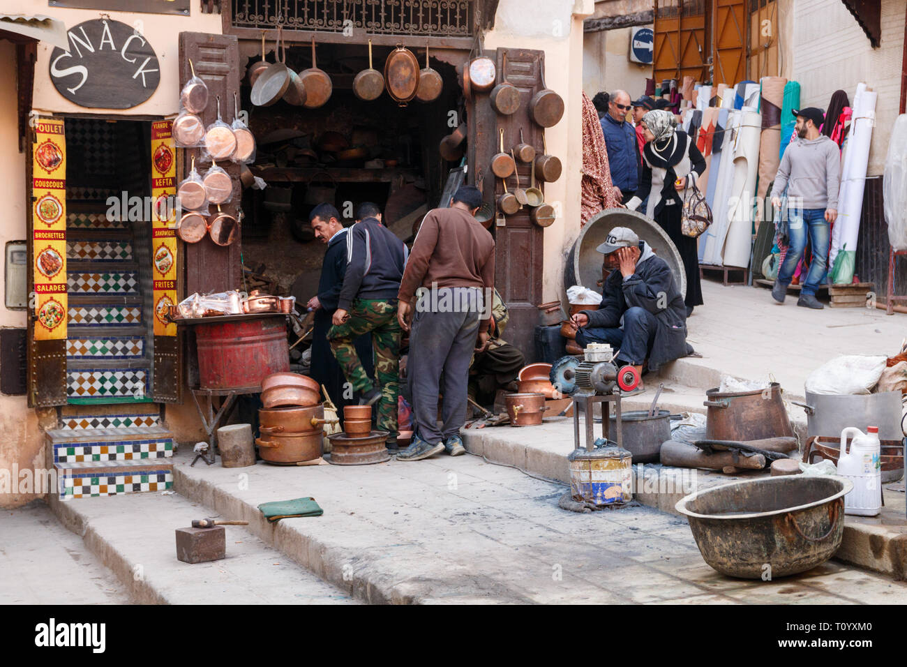 Coppersmiths crafting pots and pans in a workshop at Seffarine square in the Fez Medina, Morocco. - Stock Image