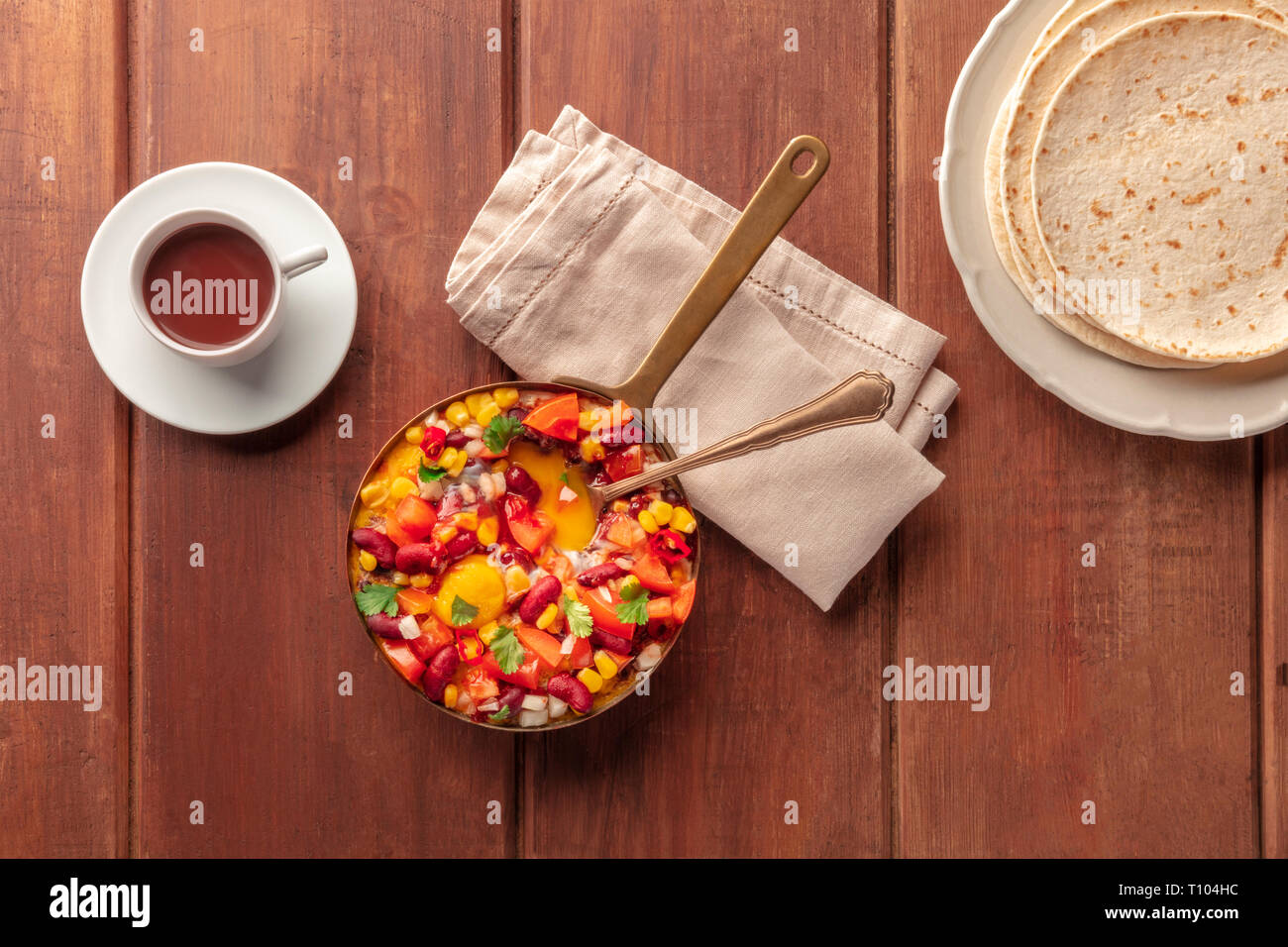 Mexican breakfast food. Huevos rancheros, baked eggs, shot from the top with pico de gallo salad, hot chocolate, and tortillas - Stock Image