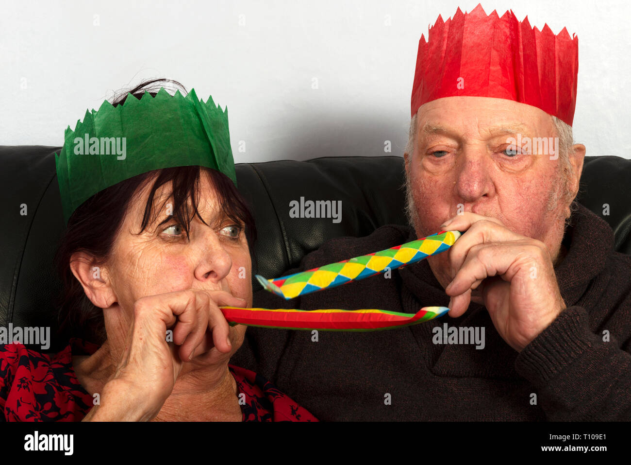 Elderly couple wearing paper Christmas cracker hats - Stock Image