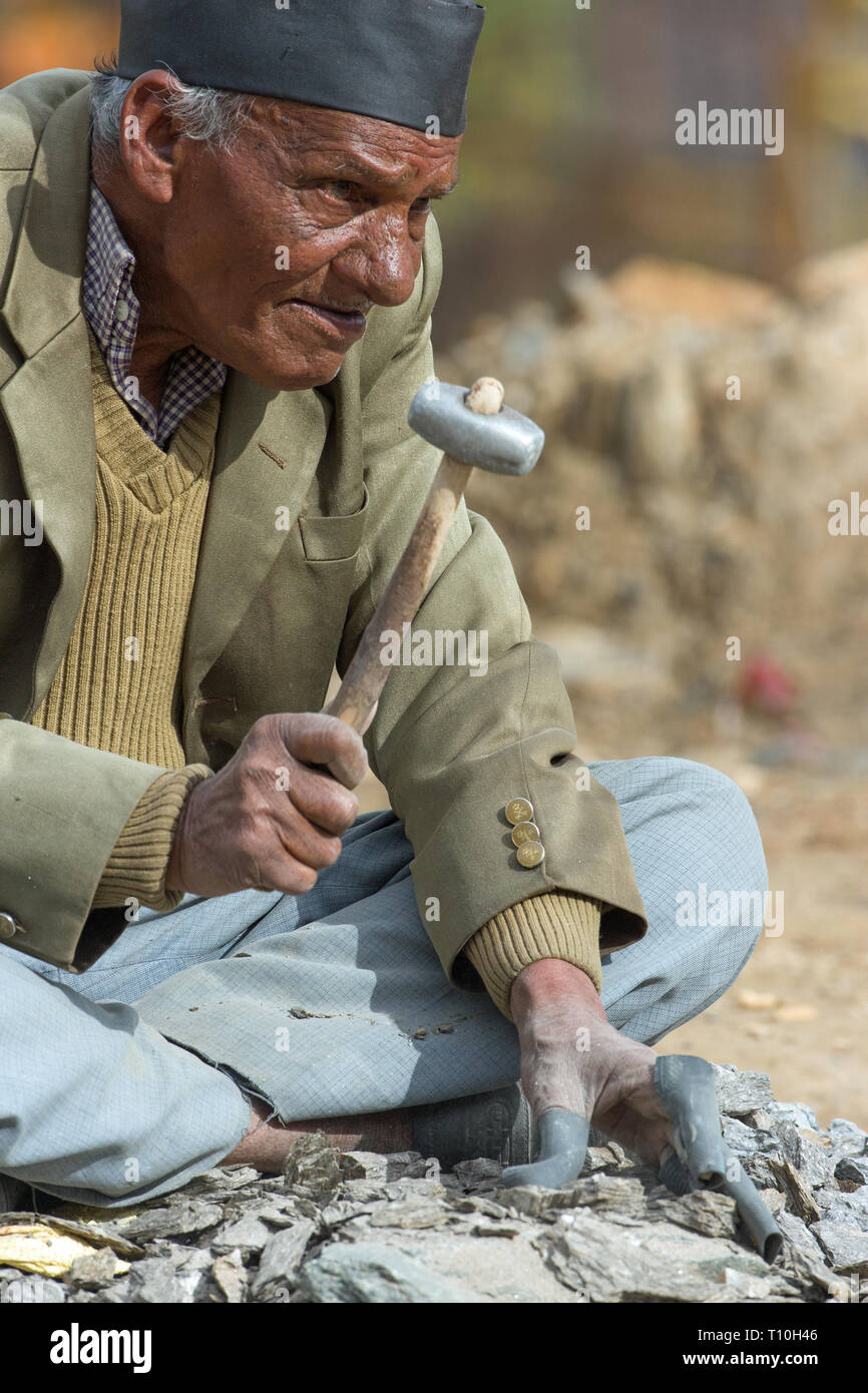 Stone Breaker. An elderly man, smashing stones down to size with a metal headed mallet, for road mending and for use in concrete mixing. Squatting alongside a mountainside village road. Northern India. - Stock Image
